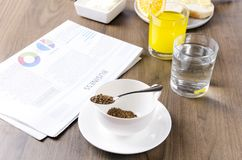 Η έννοια της επιχείρησης προετοιμάζει breakfastQuickly τον καφέ, glasss του νερού, χυμός από πορτοκάλι, εφημερίδα Πρωί επιχειρημα στοκ φωτογραφία
