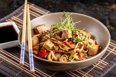 Η έννοια της ιαπωνικής κουζίνας Κινεζικά νουντλς με το κοτόπουλο, τα ψημένα στη σχάρα λαχανικά, και tofu στη σάλτσα unagi Εξυπηρε στοκ εικόνα