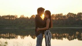 Η έννοια της οικογένειας και των σχέσεων Νέα ερωτευμένα αγκαλιάσματα ζευγών στο ηλιοβασίλεμα φιλμ μικρού μήκους