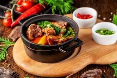 Η έννοια της σερβικής κουζίνας Juicy ψημένο βόειο κρέας στο χυμό του με τις πατάτες, τα λαχανικά και τα πράσινα Εξυπηρετήστε σε μ στοκ φωτογραφία με δικαίωμα ελεύθερης χρήσης