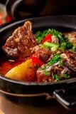 Η έννοια της σερβικής κουζίνας Juicy ψημένο βόειο κρέας στο χυμό του με τις πατάτες, τα λαχανικά και τα πράσινα Εξυπηρετήστε σε μ στοκ εικόνες