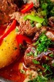 Η έννοια της σερβικής κουζίνας Juicy ψημένο βόειο κρέας στο χυμό του με τις πατάτες, τα λαχανικά και τα πράσινα Εξυπηρετήστε σε μ στοκ εικόνα