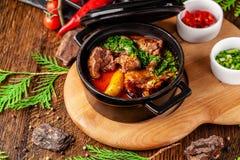 Η έννοια της σερβικής κουζίνας Juicy ψημένο βόειο κρέας στο χυμό του με τις πατάτες, τα λαχανικά και τα πράσινα Εξυπηρετήστε σε μ στοκ φωτογραφία
