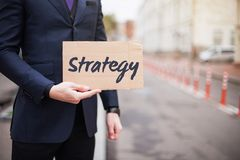 Η έννοια της στρατηγικής Ένας νέος επιχειρηματίας σε ένα επιχειρησιακό κοστούμι κρατά ένα σημάδι στο χέρι του στοκ φωτογραφίες με δικαίωμα ελεύθερης χρήσης