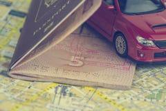 Η έννοια του αυτόματου ταξιδιού, διαβατήριο, πρότυπο ενός κόκκινου αυτοκινήτου σε έναν χάρτη υποβάθρου