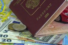 Η έννοια του αυτόματου ταξιδιού, διαβατήριο, πρότυπο ενός κόκκινου αυτοκινήτου Χρήματα 5, 10, 20 ευρώ μετρητών στο υπόβαθρο του χ στοκ εικόνα