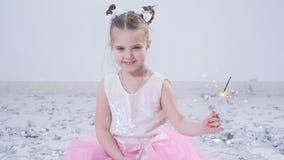Η έννοια του κόμματος και των διακοπών Ευτυχές μικρό κορίτσι σε ένα φόρεμα sparkler στο άσπρο εσωτερικό απόθεμα βίντεο