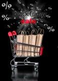 Η έννοια του μαύρου κάρρου αγορών Παρασκευής με τα τοις εκατό τσαντών εγγράφου είναι Στοκ Εικόνα