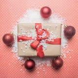 Η έννοια του νέου έτους, ένα κιβώτιο με ένα δώρο, παιχνίδια Χριστούγεννο-δέντρων σχεδιάζεται σε ένα ρόδινο υπόβαθρο με το επίπεδο στοκ φωτογραφία