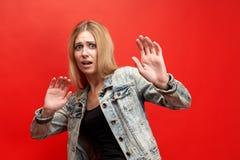 Η έννοια του φόβου, φρίκη, τρόμος Η σύγχρονη νέα κυρία στο φόβο προσπαθεί να περιφράξει μακριά τα χέρια της, με ένα εκφοβισμένο π στοκ φωτογραφία με δικαίωμα ελεύθερης χρήσης