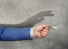 Η έννοια του χειρισμού Το χέρι που δίνει τα χρήματα στοκ εικόνες