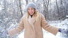 Η έννοια των διακοπών Χριστουγέννων και χειμώνα Η ευτυχής γυναίκα ρίχνει το χιόνι στο χειμερινό δάσος απόθεμα βίντεο