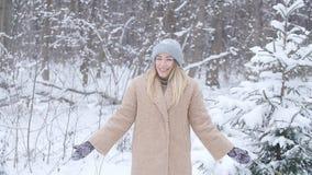 Η έννοια των διακοπών Χριστουγέννων και χειμώνα Η ευτυχής γυναίκα ρίχνει το χιόνι στο χειμερινό δάσος φιλμ μικρού μήκους