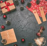 Η έννοια Χριστουγέννων, η ευχετήρια κάρτα, το κιβώτιο δώρων, τα παιχνίδια Χριστουγέννων και οι κώνοι, στο γκρίζο υπόβαθρο, διάστη στοκ εικόνες με δικαίωμα ελεύθερης χρήσης