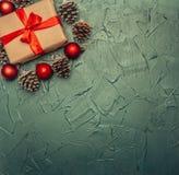 Η έννοια Χριστουγέννων, η ευχετήρια κάρτα, το κιβώτιο δώρων, τα παιχνίδια Χριστουγέννων και οι κώνοι, στο γκρίζο υπόβαθρο, διάστη στοκ εικόνες