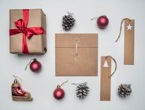 Η έννοια Χριστουγέννων, η κάρτα, το κιβώτιο δώρων, τα παιχνίδια Χριστουγέννων και οι κώνοι, στο άσπρο υπόβαθρο, επίπεδο βάζουν στοκ εικόνα