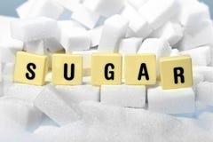 Η λέξη κεφαλαίων γραμμάτων ζάχαρης στο σωρό της ζάχαρης κυβίζει κοντά επάνω στην έννοια εθισμού Στοκ φωτογραφία με δικαίωμα ελεύθερης χρήσης