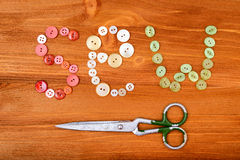 Η λέξη ράβει από τα πολύχρωμα ράβοντας κουμπιά και το ψαλίδι στο ξύλινο υπόβαθρο Στοκ Φωτογραφία