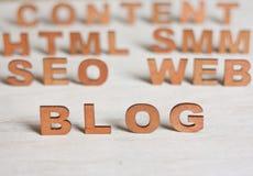 Η λέξη blog με τις ξύλινες επιστολές σε ένα υπόβαθρο θολωμένος άφησε Στοκ Εικόνες