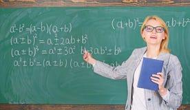 Η έξυπνη γυναίκα δασκάλων με το βιβλίο εξηγεί το θέμα κοντά στον πίνακα κιμωλίας Ο δάσκαλος σχολείου εξηγεί τα πράγματα καλά και  στοκ εικόνες