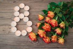 Η δέσμη όμορφου πορτοκαλιού αυξήθηκε και μικρά κεριά με μορφή αριθμός 8 οκτώ Στοκ Φωτογραφίες