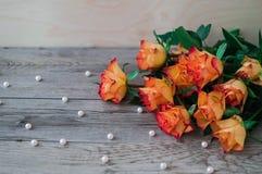 Η δέσμη όμορφου πορτοκαλιού αυξήθηκε σε ένα ανοικτό γκρι ξύλινο υπόβαθρο Στοκ Εικόνες