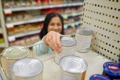 Η λήψη γυναικών μπορεί με τα τρόφιμα από το ράφι στο παντοπωλείο Στοκ Φωτογραφία