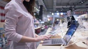 Η αίθουσα εκθέσεως συσκευών, θηλυκός αγοραστής εξετάζει το νέο lap-top κοντά στην προθήκη παρουσίασης φιλμ μικρού μήκους