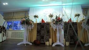Η αίθουσα συμποσίου ωραιοποιείται με τη floral διακόσμηση για τη γαμήλια τελετή απόθεμα βίντεο