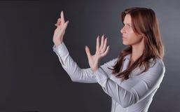 Η αβέβαιη επιχειρησιακή γυναίκα χτυπά στο εικονικό κουμπί στοκ εικόνα