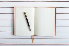 Η λαβή μελανιού βρίσκεται στην κενή σελίδα ενός σημειωματάριου Στοκ εικόνα με δικαίωμα ελεύθερης χρήσης