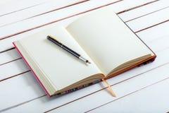 Η λαβή μελανιού βρίσκεται στην κενή σελίδα ενός σημειωματάριου Στοκ φωτογραφία με δικαίωμα ελεύθερης χρήσης