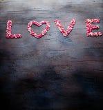Η αγάπη λέξης έκανε με τις μικρές καρδιές καραμελών, ροζ, κόκκινο, whie χρώματα, στο σκοτεινό υπόβαθρο Έννοια ημέρας βαλεντίνων ` Στοκ Εικόνα