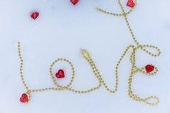 Η αγάπη επιγραφής μιας χρυσής αλυσίδας στο χιόνι δύο κόκκινες καρδιές βρίσκονται σε ένα κιβώτιο με ένα κόκκινο τόξο κορδελλών την στοκ φωτογραφία