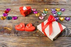 Η αγάπη λέξης σχεδίασε νέες καρδιές, δύο κιβώτια για ένα δώρο με μορφή των καρδιών και τις διακοσμητικές καρδιές στο ξύλινο υπόβα Στοκ Εικόνες