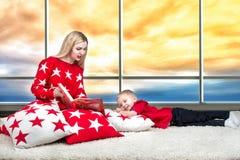 Η αγάπη της όμορφης νέας μητέρας διαβάζει ένα βιβλίο στο μικρό γιο του Να βρεθεί στα μαξιλάρια για την εσωτερική διακόσμηση στο υ στοκ φωτογραφίες με δικαίωμα ελεύθερης χρήσης