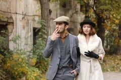 Η αγάπη του αναδρομικού ζεύγους γκάγκστερ περπατά γύρω από το παλαιό κτήριο Ο τύπος καπνίζει το πούρο ενώ το κορίτσι κοιτάζει κάτ Στοκ Εικόνα