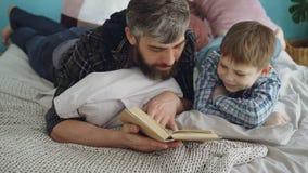 Η αγάπη του γενειοφόρου ατόμου γονέων διαβάζει το ενδιαφέρον βιβλίο στον περίεργο μικρό γιο του στο διπλό κρεβάτι στο σπίτι Πατρό απόθεμα βίντεο