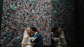 Η αγάπη του κομψού ζεύγους των newlyweds αγκαλιάζει tenderly πέρα από το ζωηρόχρωμο τοίχο απόθεμα βίντεο