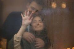 Η αγάπη του τύπου αγκαλιάζει την όμορφη φίλη του που σύρει μια καρδιά επάνω το γυαλί στοκ εικόνες