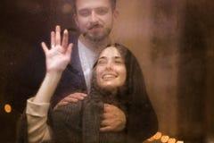 Η αγάπη του τύπου αγκαλιάζει την όμορφη φίλη του που σύρει μια καρδιά επάνω το γυαλί στοκ εικόνα με δικαίωμα ελεύθερης χρήσης