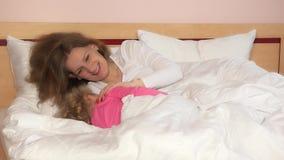Η αγάπη mom χαϊδεύει το κορίτσι παιδιών της στο κρεβάτι για να καταστήσει την πτώση κοιμισμένη απόθεμα βίντεο
