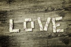 Η ΑΓΑΠΗ λέξης που γράφεται με marshmallows Έννοια ημέρας και αγάπης βαλεντίνων ` s στο ξύλινο υπόβαθρο Στοκ Εικόνες