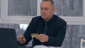 Η αγορά συνταξιούχων on-line, επιχειρηματίας με την πιστωτική κάρτα σε ένα χέρι χρησιμοποιεί το lap-top σε ένα σύγχρονο γραφείο απόθεμα βίντεο