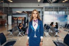 Η αεροσυνοδός θέτει στον αερολιμένα την περιμένοντας περιοχή στοκ φωτογραφίες