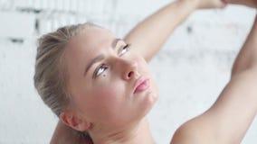 Η αθλητική καυκάσια γυναίκα κάνει την τεντώνοντας άσκηση χεριών στο στούντιο φωτός της ημέρας απόθεμα βίντεο