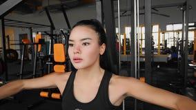Η αθλητική νέα ασιατική γυναίκα επιλύει σε έναν προσομοιωτή για το στήθος και οπλίζει τους μυς Αθλητισμός workout στη γυμναστική φιλμ μικρού μήκους