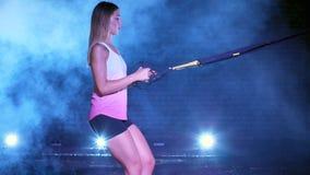 Η αθλητική, προκλητική γυναίκα εκτελεί τις ασκήσεις με το σύστημα ικανότητας trx, λουριά αναστολής TRX Τη νύχτα, στον ελαφρύ καπν φιλμ μικρού μήκους
