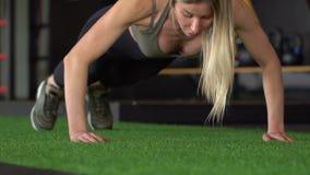 Η αθλητική όμορφη γυναίκα κάνει το ώθηση-UPS ως τμήμα της διαγώνιας ικανότητάς της, ρουτίνα κατάρτισης γυμναστικής Bodybuilding o απόθεμα βίντεο