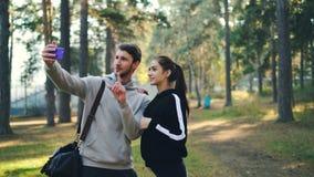 Η αθλητικοί φίλη και ο φίλος κάνουν τη σε απευθείας σύνδεση τηλεοπτική κλήση χρησιμοποιώντας το smartphone στεμένος στο πάρκο εξε απόθεμα βίντεο